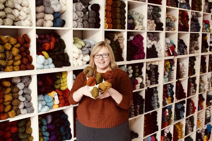 Owner Deanna Guttman in front of the wall of yarn at Needles in the Hay in downtown Peterborough, which is one of only a handful of stockists in Canada that carry the famous Brooklyn Tweed line. Needles in the Hay is launching BT by Brooklyn Tweed, two quick and fun patterns, written with the beginner knitter in mind. Great projects for gift giving, and free with with yarn purchase, they're only available until December 4th. (Photo: Amy E. LeClair)