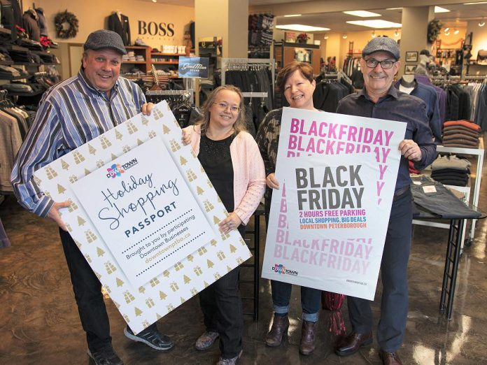Peterborough Downtown Business Improvement Area (DBIA) executive director Terry Guiel and marketing committee member Julie Morris with Gail and John Martin, owners of John Roberts Clothiers, one of 100 downtown businesses participating in Black Friday and the Holiday Shopping Passport program, where you can win prizes by choosing local first for your holiday shopping. (Photo courtesy of Peterborough DBIA)