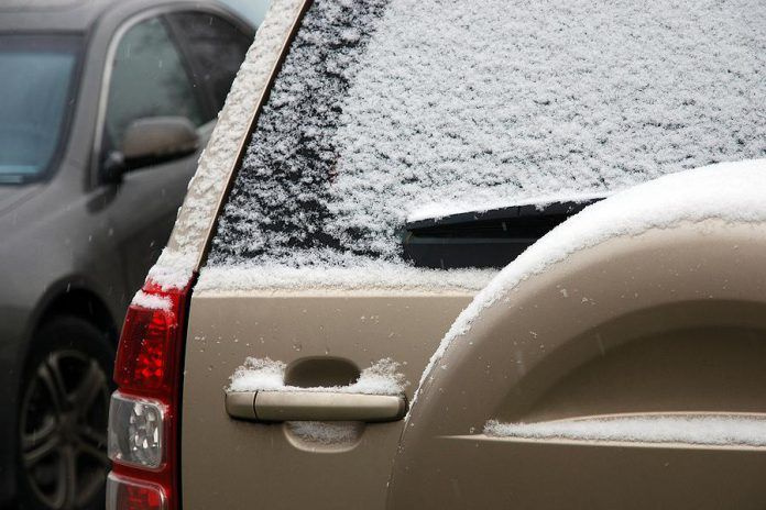 Car window covered with light snow