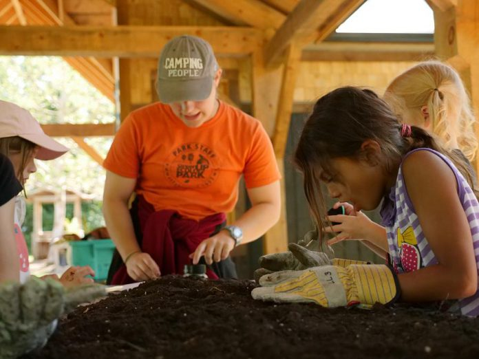 Participants in the Earth Adventures summer camp conduct a soil study within the new open-air classroom that was built in 2018 thanks to donations to GreenUP. Funds raised this holiday season will be used to install solar panels and lighting on this building, amongst other projects.  (Photo courtesy of GreenUP)