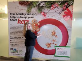 """Meghan Moloney, Charitable Giving Advisor with the Peterborough Regional Health Centre (PRHC) Foundation, adds a Grateful Hearts cookie tribute featuring a message of thanks to the PRHC Foundation's """"big plate"""" holiday display in the hospital's main lobby. By making a donation to the PRHC Foundation this holiday season, you can not only share your message or holiday greetings with doctors, nurses, and staff of our regional hospital, but your donation will help to fund needed new equipment and technology at the hospital's Cardiac Catheterization Lab, which provides life-saving care to thousands of people every year. (Photo courtesy of PRHC Foundation)"""
