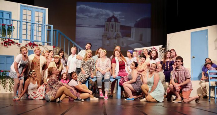 """Natalie Dorsett as Donna, Christie Freeman as Tanya, and Lyndele Gauci as Rosie (sitting on the table) with the ensemble cast of the St. James Players production of the hit musical """"Mamma Mia!"""". (Photo: Wendy Morgan)"""