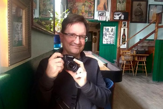 A rare photo of Peterborough photographer Andy Carroll, taken at The Only in downtown Peterborough. Preferring to stay behind his lens, Andy has quietly created an ongoing visual documentation of Peterborough's landscapes and culture, with a focus on theatre and music. (Photo: Sam Tweedle / kawarthaNOW.com)