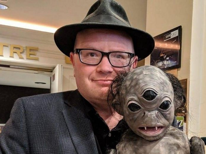 "Sam Tweedle posing with the eponymous creature of ""The Basement Monster"", a short family fantasy film by Michael Hayes and Brendan Fell. The creature in the film was created by talented Omemee FX makeup artist Rhonda Causto based on a doodle by Michael's daughter Zoe. (Photo: Mandy Rose)"