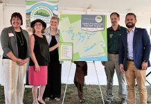 """Our look back at business and organizational news in 2019 in Peterborough and the Kawarthas includes this past summer's launch of the Trent-Severn Trail Town program, Canada's first waterway """"trail town"""" program that links communities along the Trent-Severn Waterway (including Campbellford, Hastings, Lakefield, Buckhorn, Lindsay, Bobcaygeon, Fenelon Falls, Coboconk, and Rosedale) to encourage regional tourism and support local business. Pictured at the August 22nd launch at Ranney Falls (Locks 11-12) in Campbellford (from left to right): Cycle Forward founder and trail town consultant Amy Camp, Northumberland-Peterborough South MP Kim Rudd, Kawarthas Northumberland/Regional Tourism Organization 8 (RTO8) Executive Director Brenda Wood, Parks Canada Associate Director for Ontario Waterways Dwight Blythe, and Northumberland-Peterborough South MPP David Piccini. (Photo courtesy of RTO8)"""