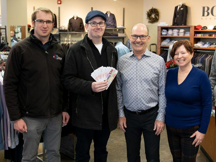 """The Peterborough Downtown Business Improvement Area (DBIA) annual Holiday Shopping Passport program rewards people when they shop, dine, or treat themselves in downtown Peterborough. Kevin Dawe of Peterborough (second from left) picked up his prize of $500 in """"downtown money"""" at John Roberts Clothiers, one of more than 150 businesses and organizations partipcating in this year's Holiday Shopping Passport program. Also pictured are Peterborough DBIA communications manager Joel Wiebe and John Roberts Clothiers owners John and Gail Martin. There are two more early bird draws for $500 in December and a grand prize draw of $1,500 in January. (Photo courtesy of Peterborough DBIA)"""