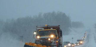 Snow plow on highway during snow squall
