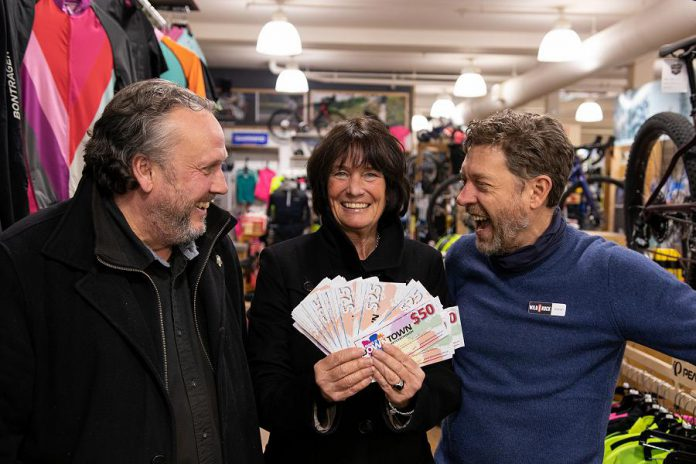 "Karen Procyk of Peterborough collects her grand prize of $1,500 in ""downtown money"" at Wild Rock Outfitters on 169 Charlotte Street after her Holiday Shopping Passport was drawn at the culmination of the annual initiative by the Peterborough Downtown Business Improvement Area (DBIA) to encourage people to choose local. Also pictured is DBIA executive director Terry Guiel (left) and Wild Rock Outfitters co-owner Kieran Andrews. (Photo courtesy of Peterborough DBIA)"