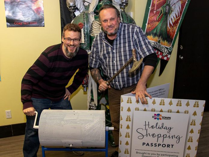The Holiday Shopping Passport program is an annual initiative by the Peterborough Downtown Business Improvement Area (DBIA) to encourage people to choose local. During the 2019 Holiday Shopping Passport Program, Downtown shoppers stamped approximately $2.3 million in downtown purchases on their passports. Pictured are DBIA executive director Terry Guiel and Dueling Grounds owner Wayne Mittlestead drawing the winning Holiday Shopping Passport, belonging to Karen Procyk of Peterborough. (Photo courtesy of Peterborough DBIA)