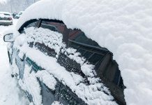 Car covered in snow in winter after blizzard
