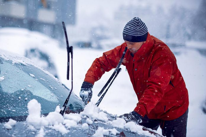 Man clearing snow and ice from car during a winter storm