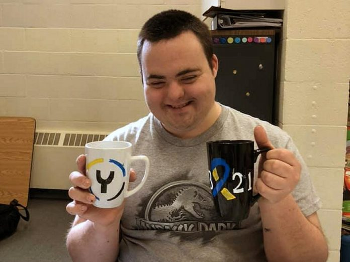 "Josh, a member of The Biz Group, displays two of the group's hand-painted mugs created for Y Drive and Peterborough Challenger Baseball. The group is also selling ""love mugs"" and plans to expand with hand-painted tote bags and t-shirts. All proceeds from the sales of items go directly to members of The Biz Group, an initiative supported by the Down Syndrome Association of Peterborough. (Photo courtesy of Down Syndrome Association of Peterborough)"