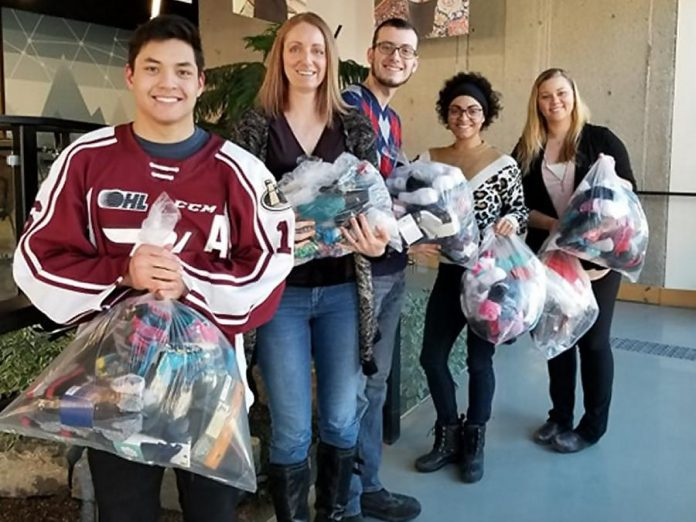 Peterborough Petes forward Nick Robertson and Heads Up for Inclusion staff with donated socks intended for Peterborough Youth Services. (Photo courtesy of Heads Up for Inclusion)