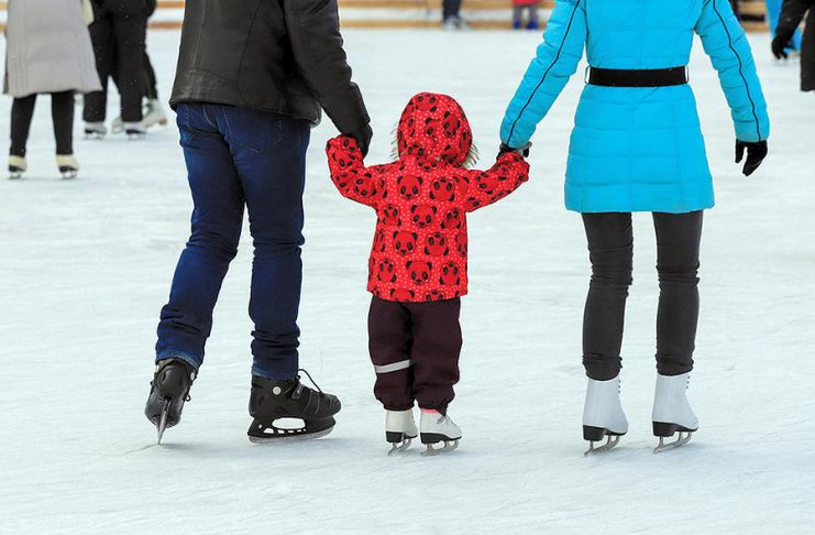Two parent teaching their young child how to skate on an outdoor rink.
