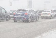 Cars on road during winter storm with snow causing poor visibility.