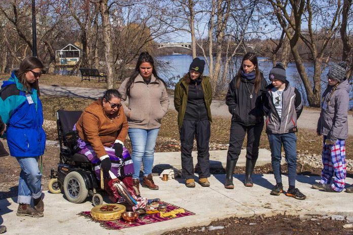 At the Depave site at 100 Water Street in downtown Peterborough, Anishinaabe elder Dorothy Taylor of the Curve Lake First Nation explains the significance of the materials she uses to perform water ceremony to students from St. Anne's Catholic Elementary School. In partnership with GreenUP's Wonders of Water program, the students are transforming a flood-prone corner of their school yard into a rain garden. They also took a tour of the local watershed, tracing Jackson Creek from its headwaters at Loggerhead Marsh to its outflow at the Otonabee River, near the Depave site. (Photo: GreenUP)