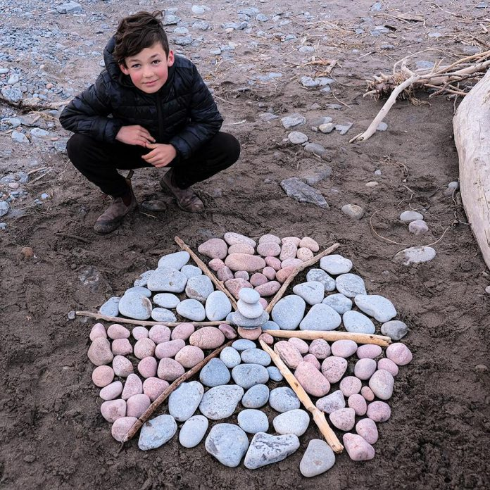 Port Hope artist Lee Higginson's son Sam with his creation at West Beach in Port Hope. Lee and her sons Sam and Charley, who are both young artists, hope to make as much public art as they can during the COVID-19 shutdown. (Photo courtesy of Lee Higginson)