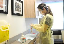Public health nurse Simone Jackson wearing personal protective equipment as she prepares to open a swab to test a patient for COVID-19 in Peterborough Public Health's clinic. (Photo courtesy of Peterborough Public Health)