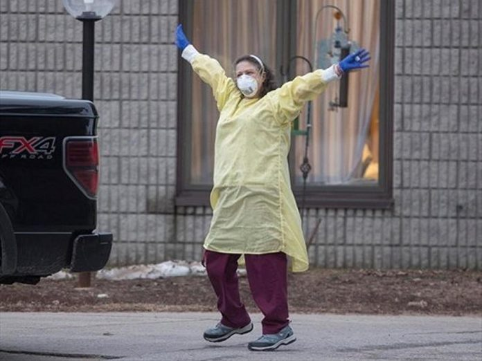 A health care worker at Pinecrest Nursing Home in Bobcaygeon, Ontario responds to passing cars honking support on Tuesday, March 31, 2020. (Photo: Fred Thornhill / The Canadian Press)