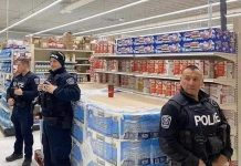 "Police officers at an unidentified location in Canada protect a skid of toilet paper. Could this become a common sight in Canada under the proposed ""Protection Of Our Paper"" (POOP) Act? (Photo source: jkooshan / reddit.com)"