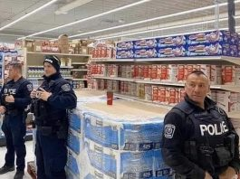 """Police officers at an unidentified location in Canada protect a skid of toilet paper. Could this become a common sight in Canada under the proposed """"Protection Of Our Paper"""" (POOP) Act? (Photo source: jkooshan / reddit.com)"""