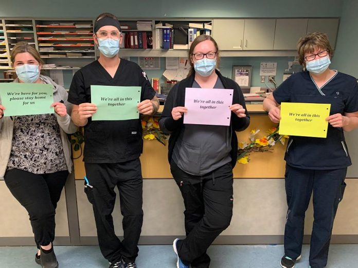 "Team members from the medical north unit at Ross Memorial Hospital in Lindsay with messages for the community: ""We're here for you, please stay home for us."" and ""We're all in this together.""  (Photo courtesy of Ross Memorial Hospital)"