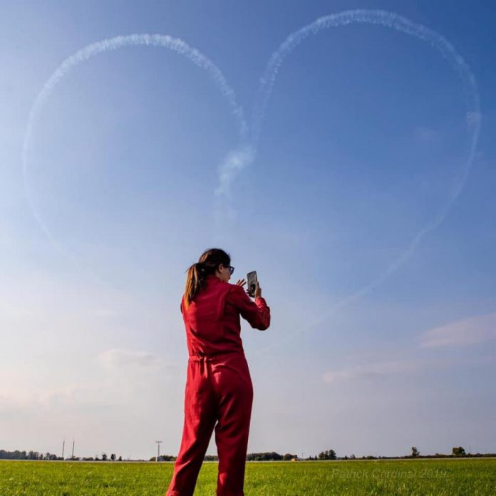 Captain Jennifer Casey taking a photo of a heart created by the Canadian Forces Snowbirds. (Photo: Patrick Cardinal / Snowbirds)