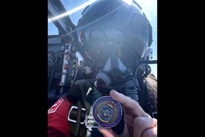 Captain Jennifer Casey in flight displaying the 1 Canadian Air Division commander's coin she received before departing Winnipeg during the Operation Inspiration. (Photo: Jenn Casey / Instagram)