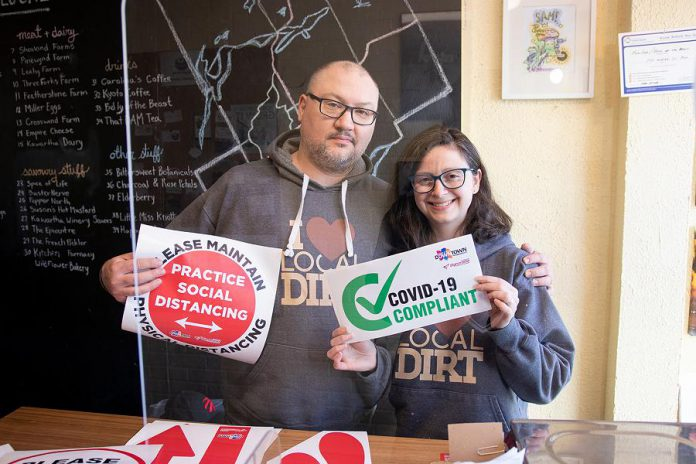 Anthony and Samantha Lennan, owners of The Food Shop on Water Street in downtown Peterborough, display one of the COVID-19 retail kits. The kits include a clear germ barrier on a stand that can be placed on a retail counter, locally sourced hand sanitizer, masks, and vinyl graphics to provide instruction and direction for customers. (Photo courtesy of Peterborough DBIA)