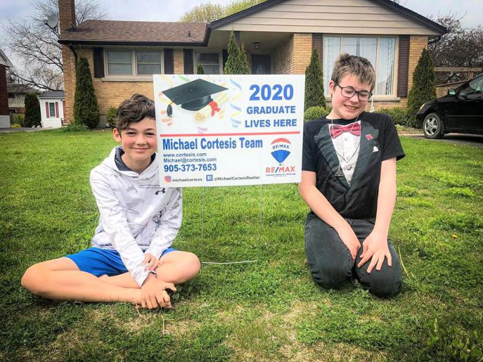 Port Hope artist Lee Higginson's sons Sam and Charley, who were both scheduled to have graduation ceremonies this year, with a sign provided by Cobourg real estate broker Michael Cortesis to help celebrate their graduations. (Photo: Lee Higginson / Facebook)