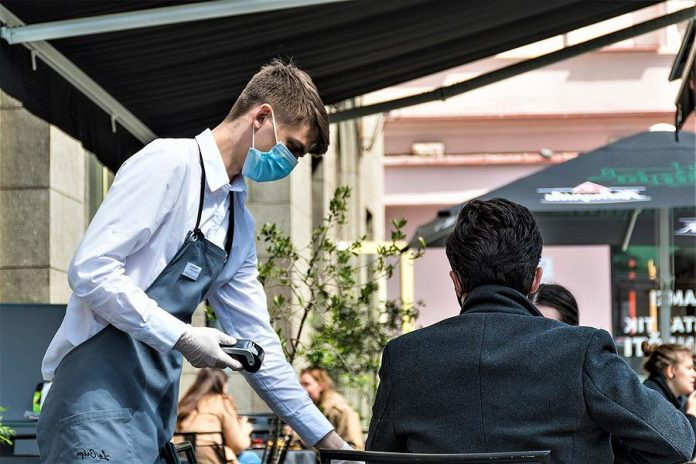 A waiter with a mask serves two customers on a patio