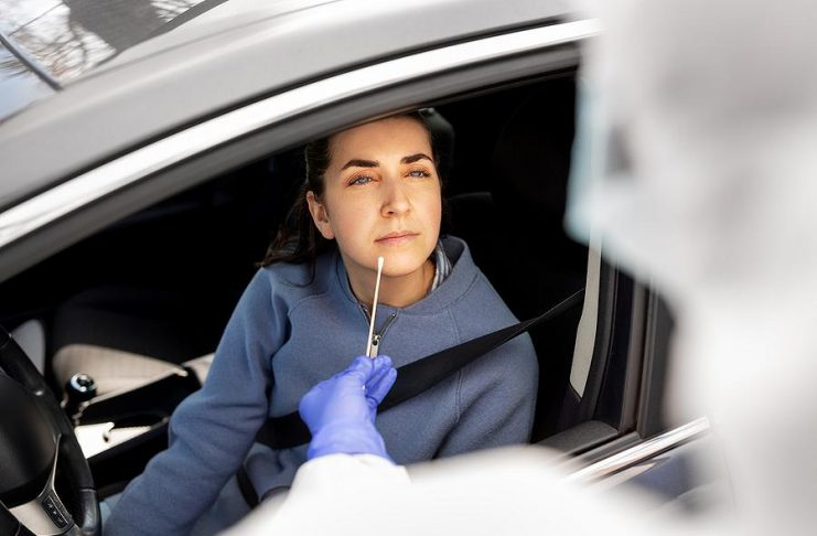 A woman being swabbed at a drive-through COVID-19 testing clinic