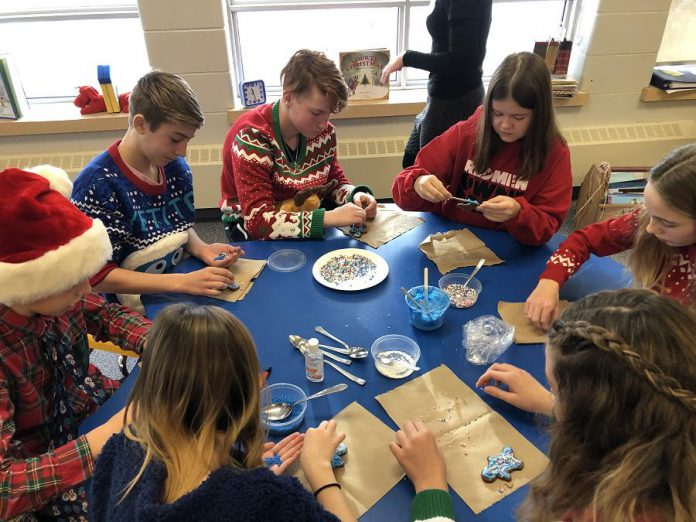 """In December 2019, Monsignor O'Donaghue students celebrated their successful water retrofit application by rotating through festive stations. At this station, students decorate gingerbread folks while brainstorming what the expression """"We are Water"""" means to them. From left to right: Lauren Graham, Nate O'Brian, Cooper Cook, Owen Cook, Sara McMahon, Isabel Brockley, and Kylie Lake. (Photo: GreenUP)"""