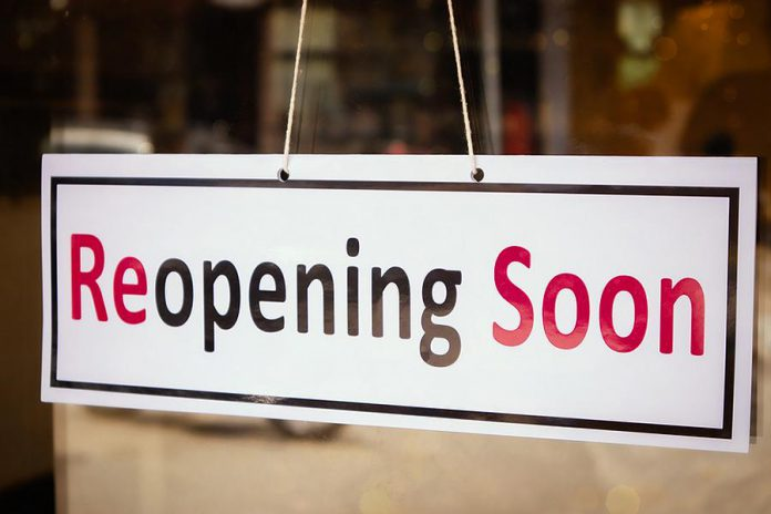 """A """"reopening soon"""" sign in the window of a business"""