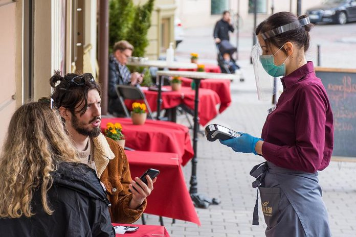 A masked waitress takes an order from customers at a restaurant in Lithuania during the COVID-19 pandemic. The Ontario government is considering a regional approach to reopening the province during the pandemic, in which restrictions would be loosened sooner in regions such as Peterborough that have low rates of COVID-19 cases. (Photo: Michele Ursi)