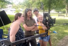 """Filmmaker Jamie Oxenham (second from left) with script supervisor Michelle Foster, sound technician Jake Phair, and production assistant Kat Shaw watching actors Steve Kasan and Rick Amsbury (not pictured) during the shooting of """"Abra Kadabra"""" in Lindsay's Victoria Park. (Photo: Sam Tweedle / kawarthaNOW.com)"""