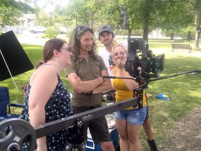"Filmmaker Jamie Oxenham (second from left) with script supervisor Michelle Foster, sound technician Jake Phair, and production assistant Kat Shaw watching actors Steve Kasan and Rick Amsbury (not pictured) during the shooting of ""Abra Kadabra"" in Lindsay's Victoria Park. (Photo: Sam Tweedle / kawarthaNOW.com)"