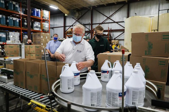 Premier Doug Ford packing bottles of disinfectant into boxes into boxes during a tour of Charlotte Products in Peterborough, which ramped up production of its cleaning products during the pandemic. Ford then travelled to Bobcaygeon for a tour of Kawartha Dairy. (Photo: Government of Ontario)