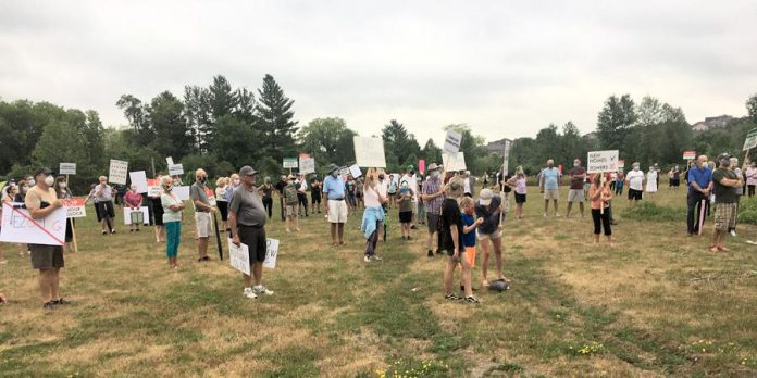 A large crowd gathered Thursday night (July 16) at the site of a proposed seven-storey apartment building at Armour Road and Cunningham Boulevard to rally against the project, citing increased traffic and flooding concerns, and with no stores within walking distance of the neighbourhood, the pending loss of the site's commercial use designation.  (Photo: Paul Rellinger / kawarthaNOW.com)