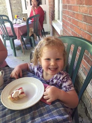 A young visitor enjoys a fresh-baked scone with preserves and whipped cream at a past Scottish Tea at Hutchison House in Peterborough. This year will see some changes in the tea service due to COVID-19. (Photo: Hutchison House / Facebook)