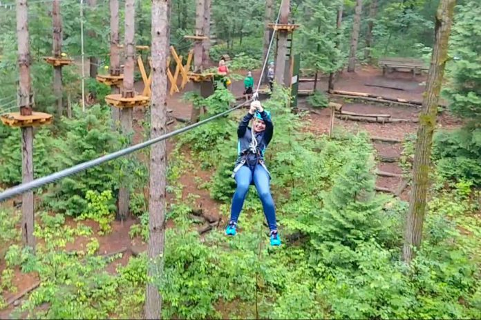 kawarthaNOW writer Paula Kehoe rides the zipline at Treetop Trekking in the Ganaraska Forest near Port Hope in 2017. Guests can will see changes at Treetop Trekking parks this year due to COVID-19, including fewer people in the area at one time, staff wearing personal protective equipment (PPE), hand sanitizer being readily available, and augmented cleaning procedures. (Screenshot)