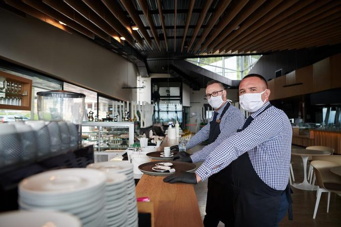 Two masked employees in a restaurant. (Stock photo)