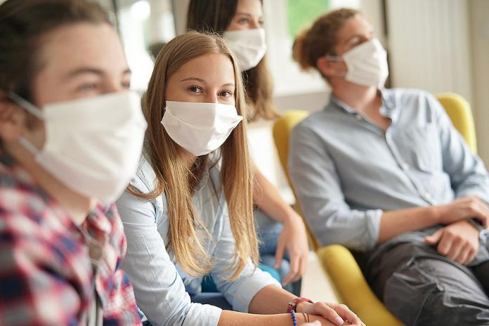 Young people wearing masks during COVID-19 pandemic. (Stock photo)