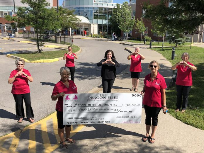 Ross Memorial Hospital Foundation CEO Erin Coons (centre) with members of The Dragon Flies Breast Cancer Survivor Group on August 19, 2020, celebrating the group's $10,000 donation to the foundation for breast cancer health at the Lindsay hospital (from left to right): Maria Bennett, Carol Wilson (holding sign), Kelly Solotarow, Janet Mackey, Jane Graham (holding sign), and Cecile Parker. (Photo courtesy of Ross Memorial Hospital Foundation)
