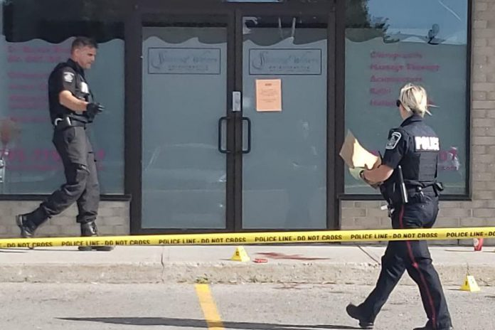 Police investigate a double stabbing on the morning of August 18, 2020 at Market Plaza, located at the corner of George and Rink streets in Peterborough, that injured a 50-year-old man and an 18-year-old man. Police evidence markers and blood can be seen on the sidewalk and in the parking lot. (Photo courtesy of Marianne Vandelinde)