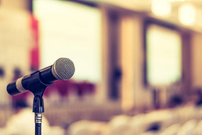 A microphone in an empty meeting space. (Stock photo)