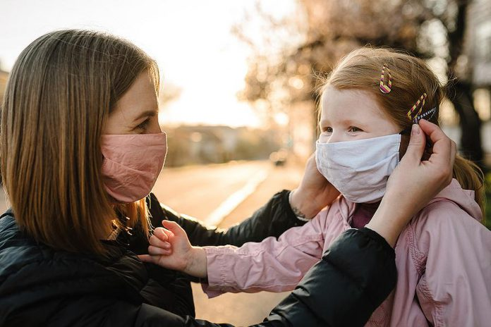 A mother and young girl wearing masks because of the COVID-19 pandemic. (Stock photo)