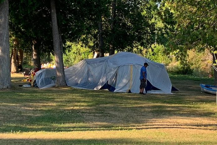 A kawarthaNOW.com reader who wishes to remain anonymous submitted this photo on August 1, 2020 of a large tent with about 30 people along River Road between Peterborough and Lakefield. Camping on Parks Canada land in this area is prohibited, and there are no public washrooms. (Supplied photo)