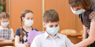 Students in a classroom and their teacher wearing face masks. (Stock photo)