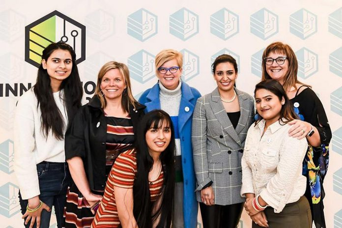 "Manjit Minhas (second from right, back row) in March 2020 with local business people Dawn Hennessey (second from left, back row), Rhonda Barnet (centre, back row), and Sofie Andreou (right, back row), founders of FemSteamPtbo, an organization supporting  young females in the Peterborough area to pursue education and career options in STEAM and skilled trades.  Minhas, a Canadian entrepreneur, venture capitalist, and self-described beer baroness who is one of the celebrity investors on CBC Television's popular Dragons' Den series, was the guest speaker at the Innovation Cluster's Electric City Talks series with a talk entitled ""Empowering Women: Achieving Business Success in Male-Dominated Industries"".  (Photo courtesy of Innovation Cluster - Peterborough and the Kawarthas)"